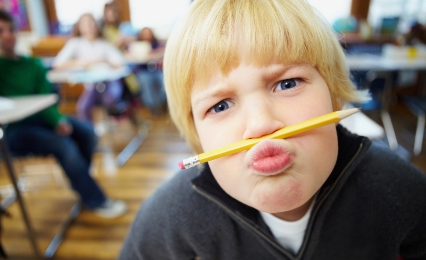 Funny young boy balancing a pencil on his nose at school